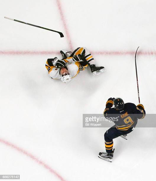 Sidney Crosby of the Pittsburgh Penguins reacts after being highsticked in the mouth by Evander Kane of the Buffalo Sabres late in their NHL game at...