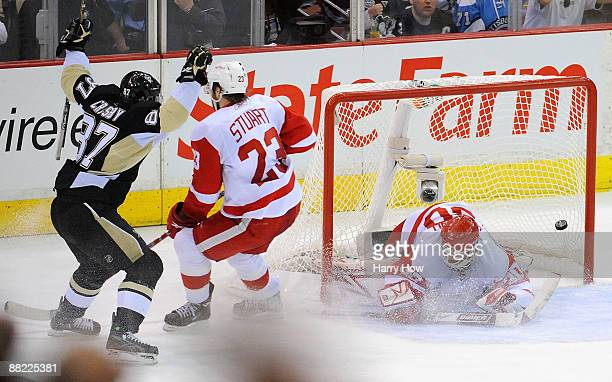 Sidney Crosby of the Pittsburgh Penguins scores a goal past goaltender Chris Osgood and Brad Stuart of the Detroit Red Wings in the second period...