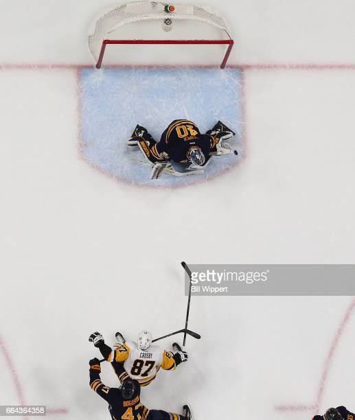 Sidney Crosby of the Pittsburgh Penguins scores a late first period onehanded goal against Robin Lehner of the Buffalo Sabres while defended by Zach...