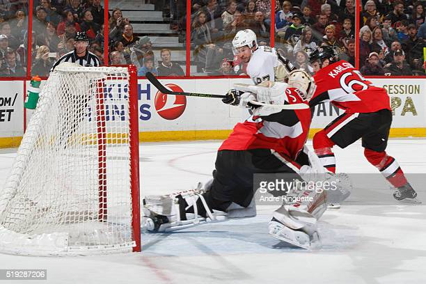 Sidney Crosby of the Pittsburgh Penguins scores a send period backhand goal against Andrew Hammond and Erik Karlsson of the Ottawa Senators at...