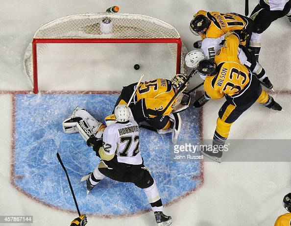 Sidney Crosby of the Pittsburgh Penguins scores against Pekka Rinne of the Nashville Predators at Bridgestone Arena on October 25 2014 in Nashville...