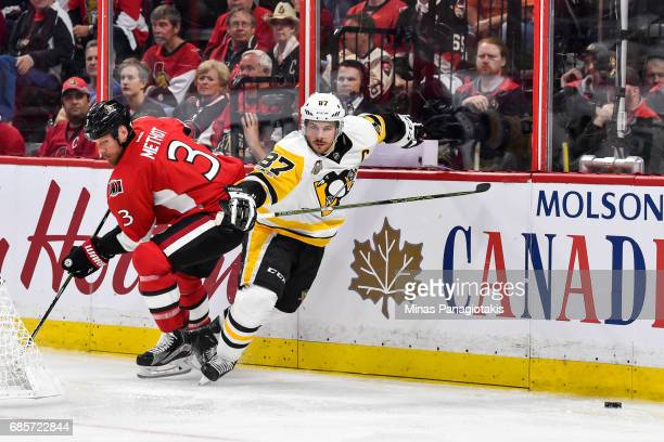 Sidney Crosby of the Pittsburgh Penguins sidesteps a hit from Marc Methot of the Ottawa Senators in Game Three of the Eastern Conference Final during...