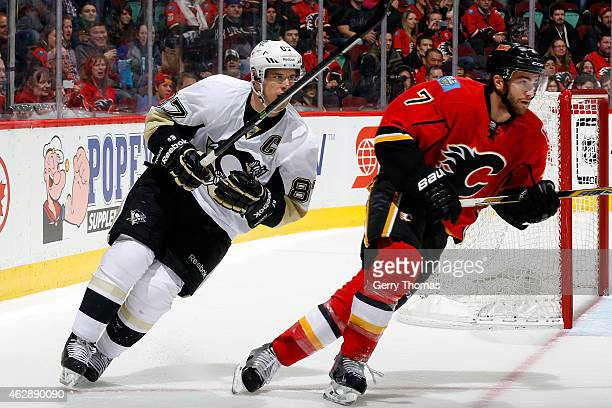 Sidney Crosby of the Pittsburgh Penguins skates against TJ Brodie of the Calgary Flames at Scotiabank Saddledome on February 6 2015 in Calgary...