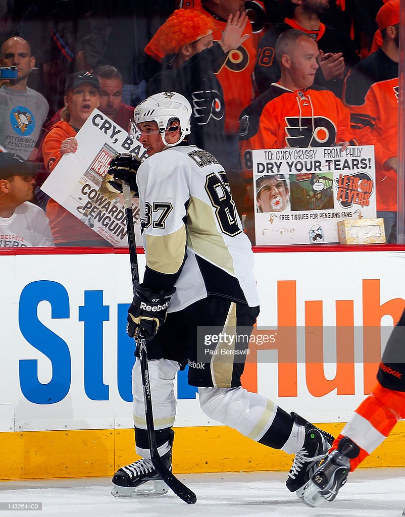 Sidney Crosby #87 of the Pittsburgh Penguins skates past Philadelphia Flyers fans holding signs referring to him as he tries to pressure the Flyers late in the third period of Game Six of the Eastern Conference Quarterfinals as the Flyers eliminated the Penguins by winning the game 5-1 during the 2012 NHL Stanley Cup Playoffs at Wells Fargo Center on April 22, 2012 in Philadelphia, Pennsylvania.