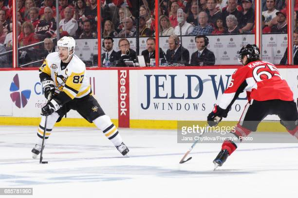 Sidney Crosby of the Pittsburgh Penguins skates with the puck against Erik Karlsson of the Ottawa Senators in Game Three of the Eastern Conference...