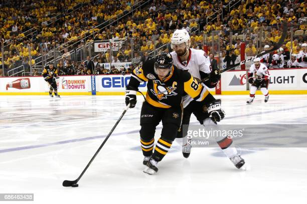 Sidney Crosby of the Pittsburgh Penguins skates with the puck against Tommy Wingels of the Ottawa Senators in Game Five of the Eastern Conference...