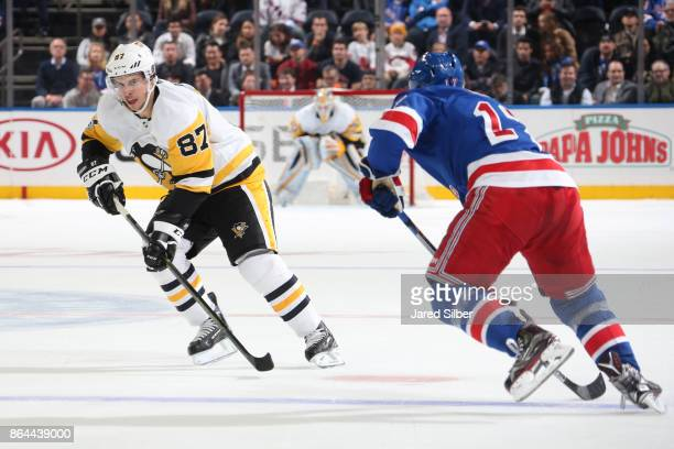 Sidney Crosby of the Pittsburgh Penguins skates with the puck against Jesper Fast of the New York Rangers at Madison Square Garden on October 17 2017...