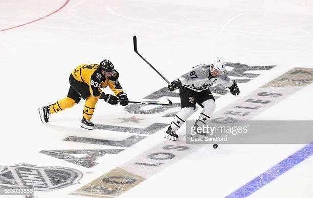 Sidney Crosby of the Pittsburgh Penguins skates with the puck as Brad Marchand of the Boston Bruins pursues during the Metropolitan Division and...
