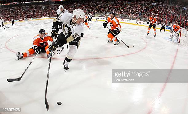 Sidney Crosby of the Pittsburgh Penguins skates with the puck in the corner against the defense of Darroll Powe and Kimmo Timonen of the Philadelphia...