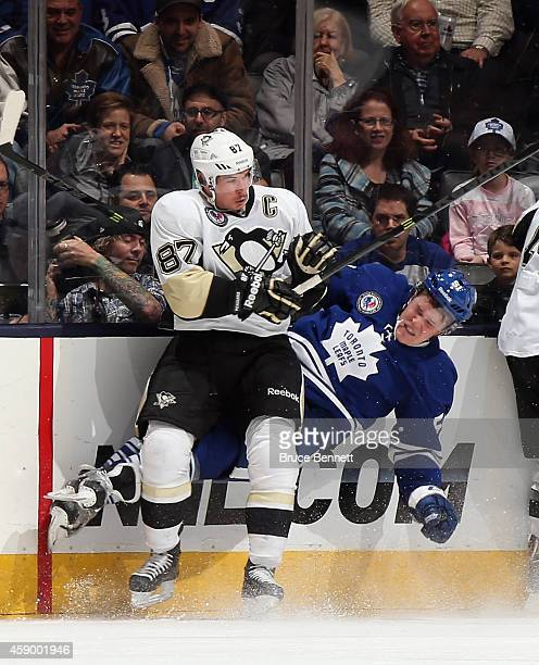 Sidney Crosby of the Pittsburgh Penguins slams Jake Gardiner of the Toronto Maple Leafs into the boards during the third period at the Air Canada...