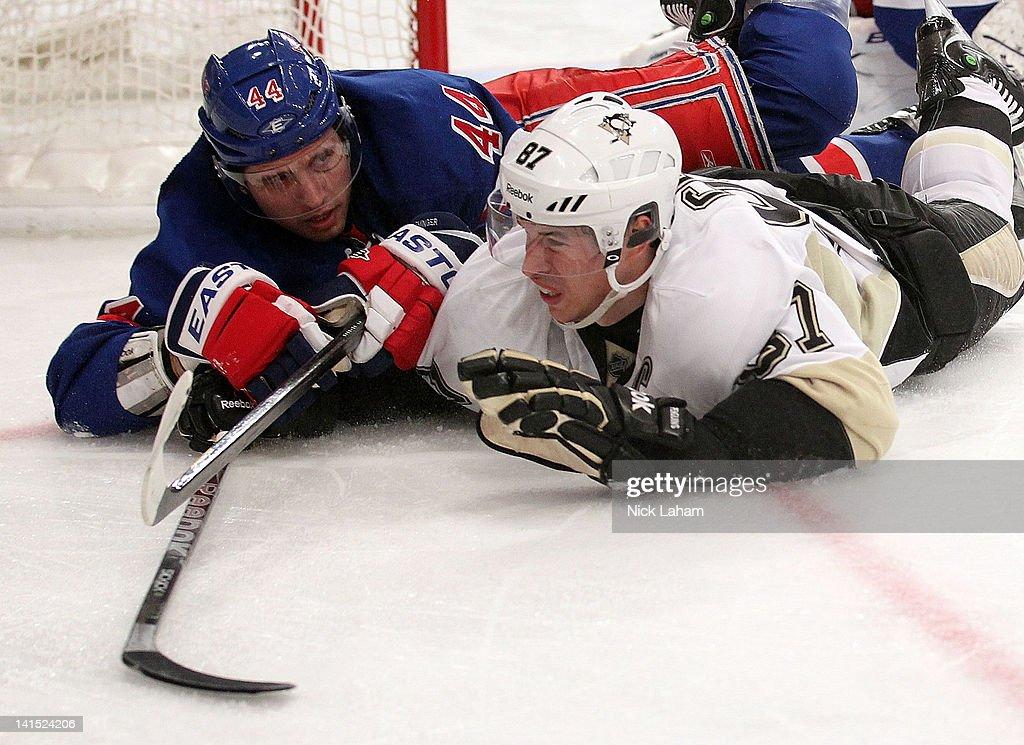 Sidney Crosby of the Pittsburgh Penguins slides across the ice alongside Steve Eminger of the New York Rangers at Madison Square Garden on March 15...