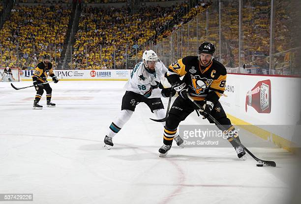 Sidney Crosby of the Pittsburgh Penguins stickhandles the puck along the left wing boards away from Melker Karlsson of the San Jose Sharks during the...