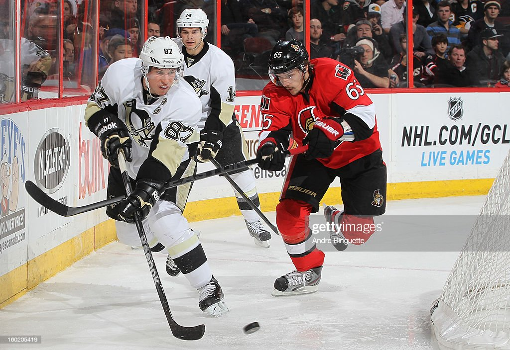 Sidney Crosby #87 of the Pittsburgh Penguins stickhandles the puck behind the net against Erik Karlsson #65 of the Ottawa Senators on January 27, 2013 at Scotiabank Place in Ottawa, Ontario, Canada.