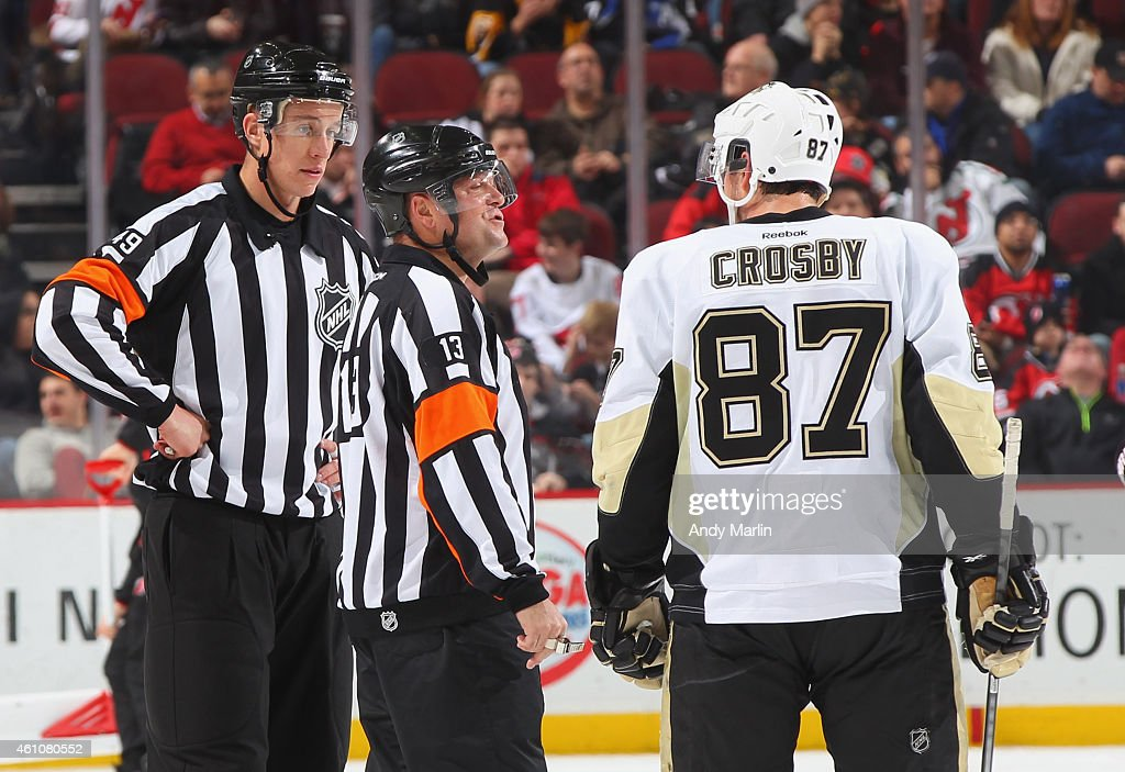 Sidney Crosby of the Pittsburgh Penguins talks to referee Dan O'Halloran and TJ Luxmore during the game against the New Jersey Devils at the...