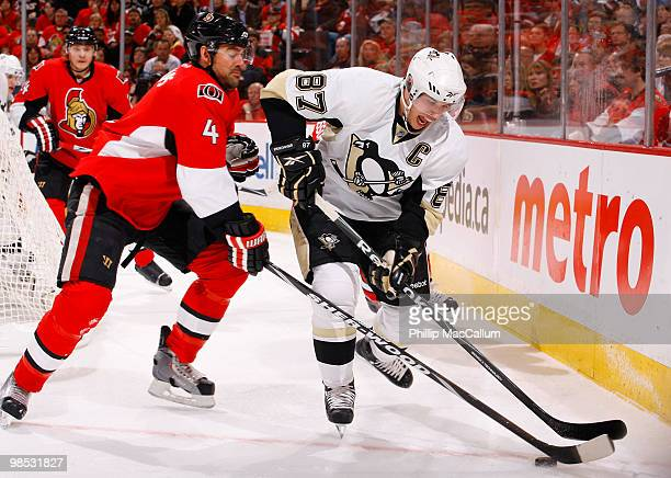 Sidney Crosby of the Pittsburgh Penguins tries to control the puck down low while fighting off the close checking of Chris Phillips of the Ottawa...