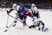 Sidney Crosby Robert Bortuzzo and Evgeni Malkin of the Pittsburgh Penguins battle for the puck against Mats Zuccarello of the New York Rangers in...
