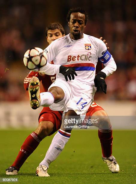 Sidney Govou of Lyon battles with Emiliano Insua of Liverpool during the UEFA Champions League Group E match between Liverpool and Lyon at Anfield on...