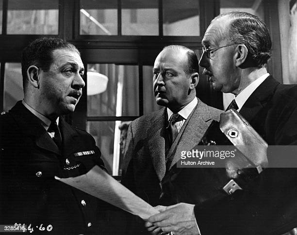 Sidney James plays a policeman opposite Cecil Parker and George Ralph in a scene from the film 'I Believe In You' directed by Basil Dearden and...