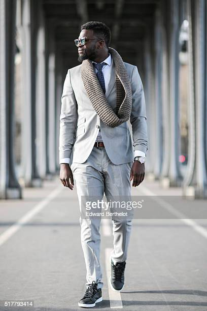 Sidya Sarr is wearing a Zara gray suit a Zara tie a Versace watch a Mango brown scarf an Illegitime white shirt and Rayban sunglasses during a street...
