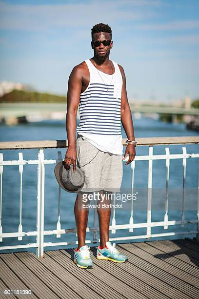 Sidya Sarr is wearing Adidas Torsion ZX 9000 shoes a gray HM short an Asos wallet chain a sleeveless tshirt from Zara a gray hat from Zara Ray Ban...