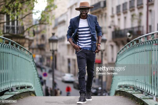 Sidya Sarr wears a Zara jacket an Andreas Osten watch Nike Blazer shoes from Shinzo Lab a Coq Sportif striped top Cheap Mondays pants and a hat from...