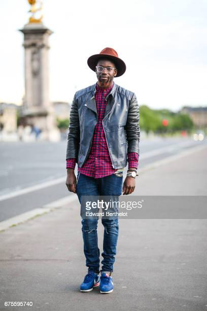 Sidya Sarr wears a Zara red tartan shirt an Asos leather perfecto black jacket Nike Cortez blue sneakers shoes a Zara hat Asos blue denim ripped...