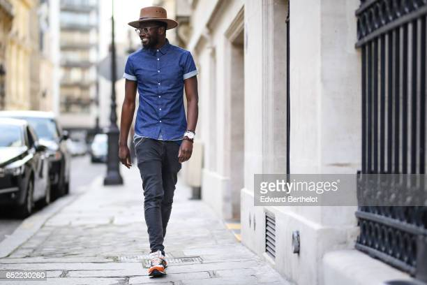 Sidya Sarr wears an Ice watch Asos black denim jeans New Balance sneakers shoes an Asos blue shirt an Asos beige hat on March 11 2017 in Paris France