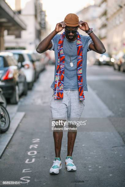 Sidya Sarr wears an orange beanie hat sunglasses a red scarf a gray tshirt a gray short and sneakers shoes on April 9 2017 in Paris France