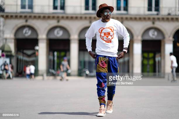 Sidya Sarr wears Nike Blazer shoes Rayban sunglasses a Dirty Nerdy white pull over with a printed teddy bear a Zara hat and colorful pants designed...