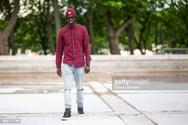 Sidya Sarr wears Zara blue denim ripped jeans Nike Blazer brown sneakers from Shinzo Paris a tshirt from Eleven Paris a Zara tartan red shirt a...