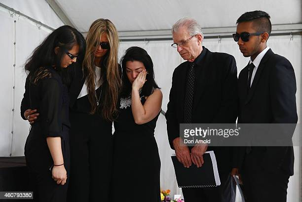 Siege victims Fiona Ma Selina Win Pe Harriette Denny and Joel Herat comfort each other at a wreath laying ceremony after the funeral for Tori Johnson...