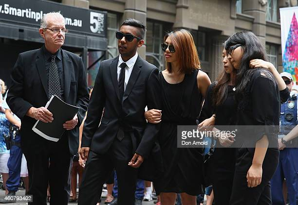 Siege victims Joel Herat Elly Chen and Fiona Ma pay their respects at wreath laying ceremony after the funeral for Tori Johnson at Martin Place on...