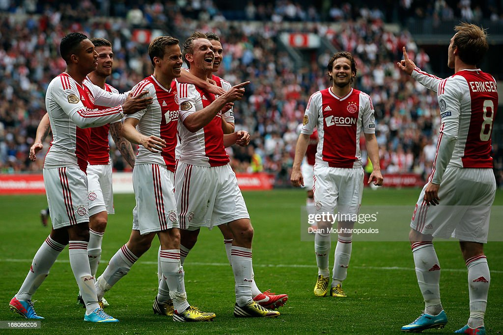 Siem De Jong (#10) of Ajax is congratulated by team mates after he score the fourth goal of the match and Christian Eriksen (#8) for setting it up with his corner during the Dutch Eredivisie match between Ajax and Willem II Tilburg at Amsterdam Arena on May 5, 2013 in Amsterdam, Netherlands.
