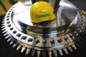 A Siemens AG branded hard hat sits on a component for a gas turbine propellers for use in power plants at the company's factory in Berlin Germany on...