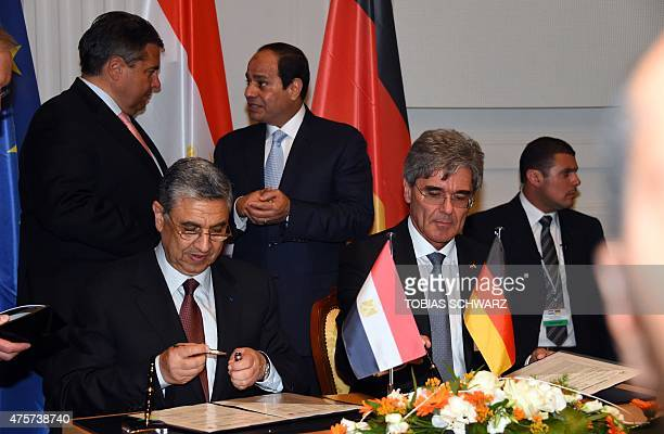 Siemens CEO Joe Kaeser and Egypt's Minister for Electricity and Energy Mohamed Shaker ElMarkabi sign a contract as German Vice Chancellor Economy and...