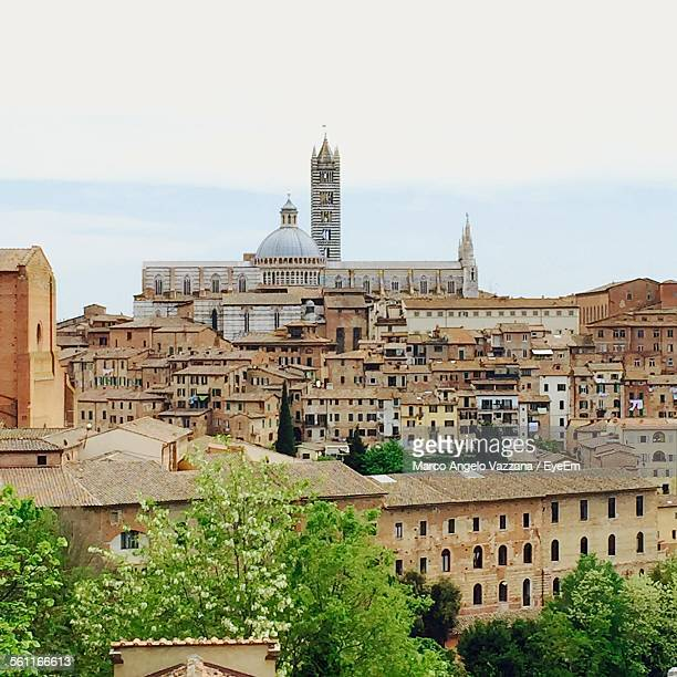 Siena Cathedral Amidst Buildings In City Against Sky