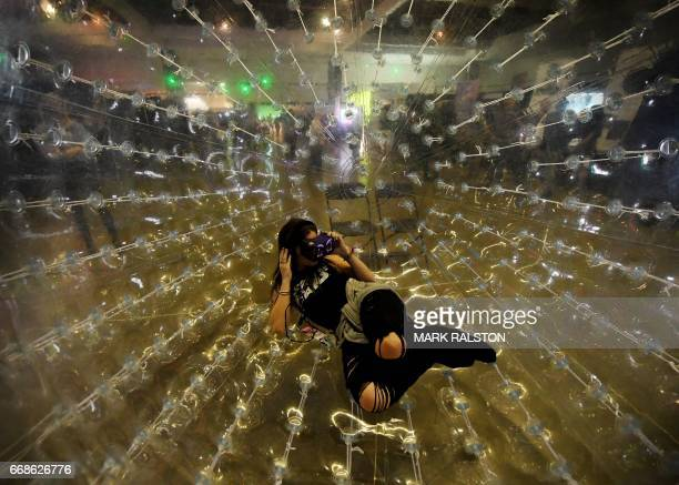 Siena Oberman tries out a virtual reality headset as she watches a production by French artist Octave Perrault while sitting in a giant bubble to...