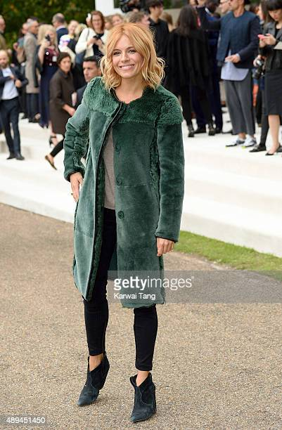 Sienna Miller attends the Burberry Prorsum show during London Fashion Week Spring/Summer 2016/17 at Kensington Gardens on September 21 2015 in London...