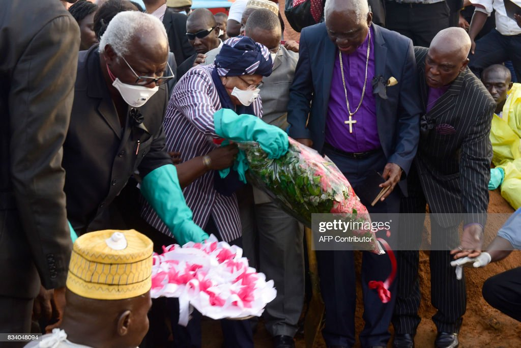 Sierra Leone President Ernest Bai Koroma (2nd L) and Liberian President Helen Johnson Sirleaf (C) lay flowers on coffins of mudslide victims on August 17, 2017 at Waterloo cemetery near Freetown, Sierra Leone. Sierra Leone buried at least 300 victims of devastating floods on Thursday, as fears grew of more mudslides and accusations of government 'inaction' over deforestation and poor urban planning mounted. With the aim of clearing the overflowing central morgue, burials began around 1800 GMT in Waterloo, a nearby town where many victims of the Ebola crisis that hit the nation in 2014 were also laid to rest, according to a morgue official and an AFP journalist at the scene. PHOTO / SEYLLOU
