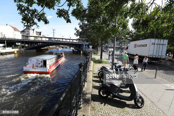 A sightseeing barge sails past a row of Coup eScooter electric hire vehicles operated by Robert Bosch GmbH as they stand on a bank of the River Spree...