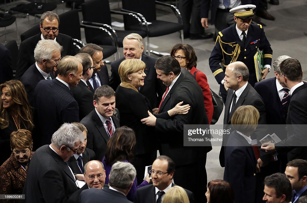 Sigmar Gabriel (Center), Chairman of German Social Democrats (SPD) hug German Chancellor Angela Merkel after a joint session of the two governments during the 50th anniversary celebration of the Elysee Treaty at Reichstag, the seat of the German Parliament (Bundestag) on January 22, 2013 in Berlin.