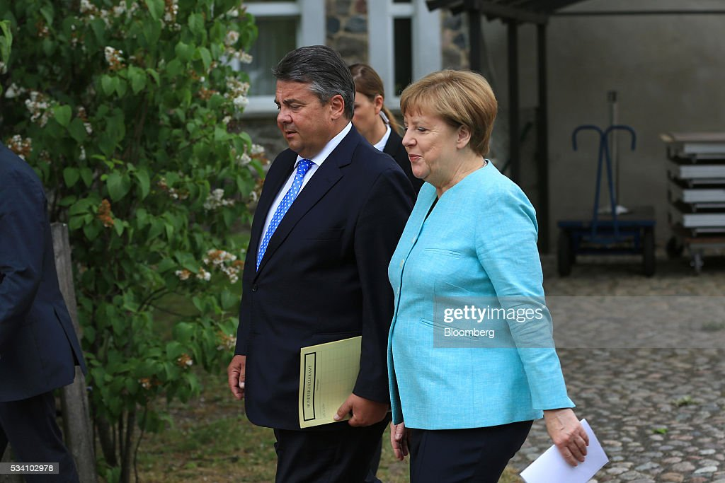 Sigmar Gabriel, Germany's economy and energy minister, center, and Angela Merkel, Germany's chancellor, depart a news conference following a two-day cabinet retreat in Meseburg, Germany, on Wednesday, May 25, 2016. In the latest response to the refugee crisis that's dogged Merkel since last summer, her cabinet on Wednesday backed legislation that includes stricter requirements for asylum seekers to integrate into German society. Photographer: Krisztian Bocsi/Bloomberg via Getty Images *** Angela Merkel; Sigmar Gabriel
