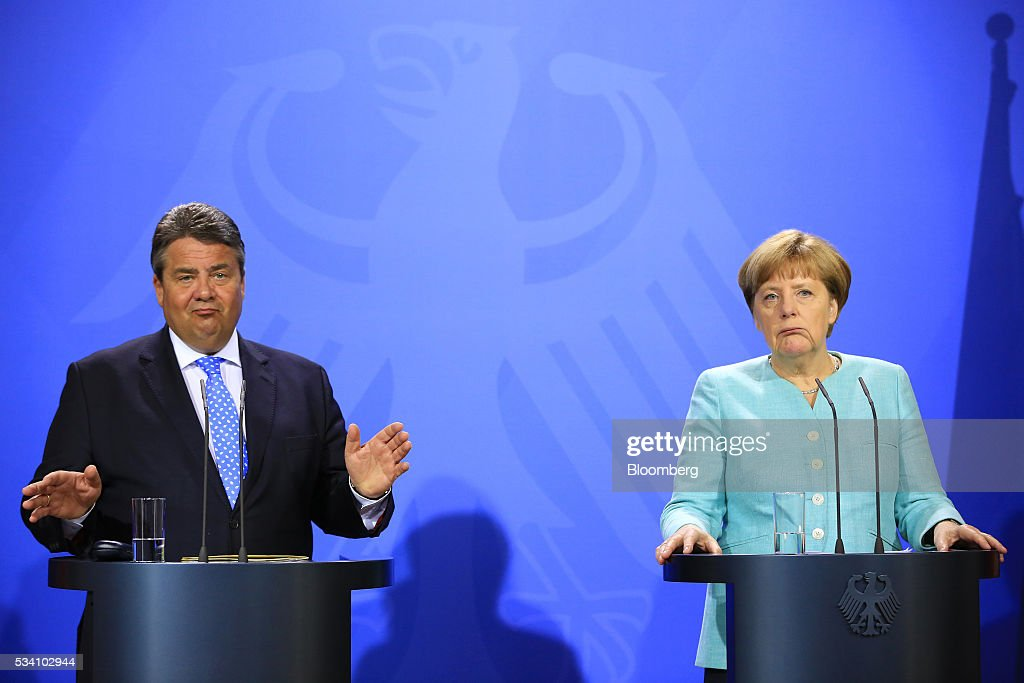 Sigmar Gabriel, Germany's economy and energy minister, left, gestures as Angela Merkel, Germany's chancellor, looks on during a news conference following a two-day cabinet retreat in Meseburg, Germany, on Wednesday, May 25, 2016. In the latest response to the refugee crisis that's dogged Merkel since last summer, her cabinet on Wednesday backed legislation that includes stricter requirements for asylum seekers to integrate into German society. Photographer: Krisztian Bocsi/Bloomberg via Getty Images *** Angela Merkel; Sigmar Gabriel
