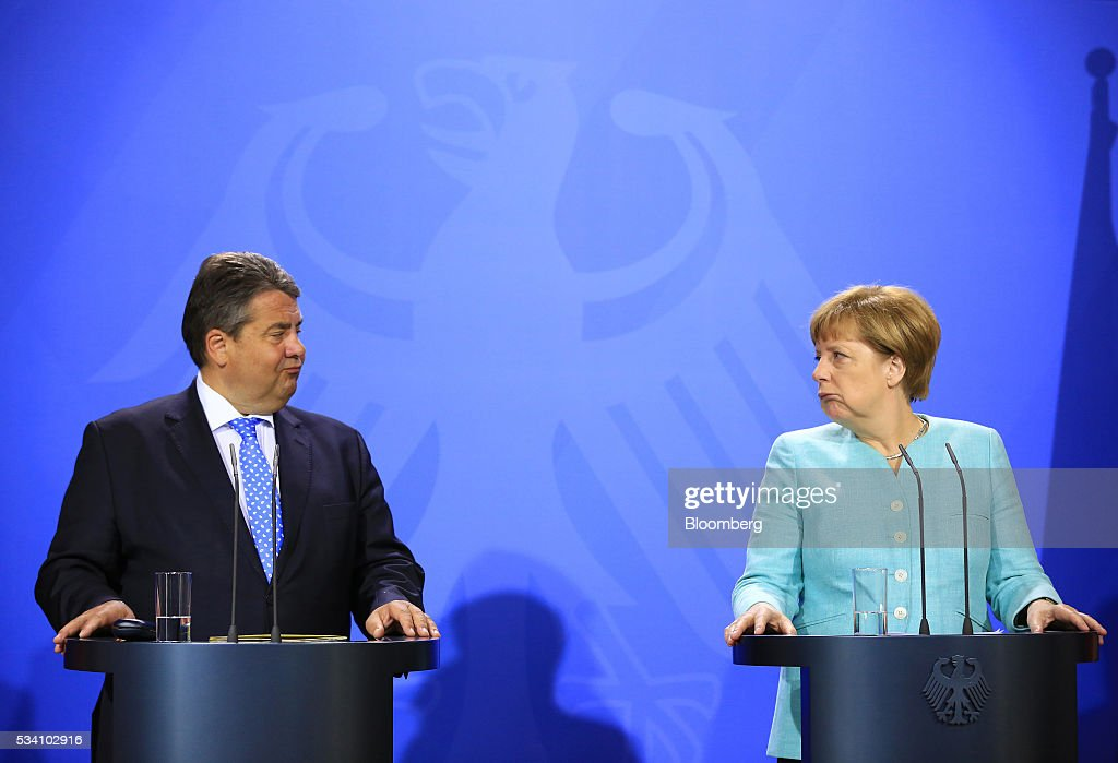 Sigmar Gabriel, Germany's economy and energy minister, left, looks towards Angela Merkel, Germany's chancellor, during a news conference following a two-day cabinet retreat in Meseburg, Germany, on Wednesday, May 25, 2016. In the latest response to the refugee crisis that's dogged Merkel since last summer, her cabinet on Wednesday backed legislation that includes stricter requirements for asylum seekers to integrate into German society. Photographer: Krisztian Bocsi/Bloomberg via Getty Images *** Angela Merkel; Sigmar Gabriel