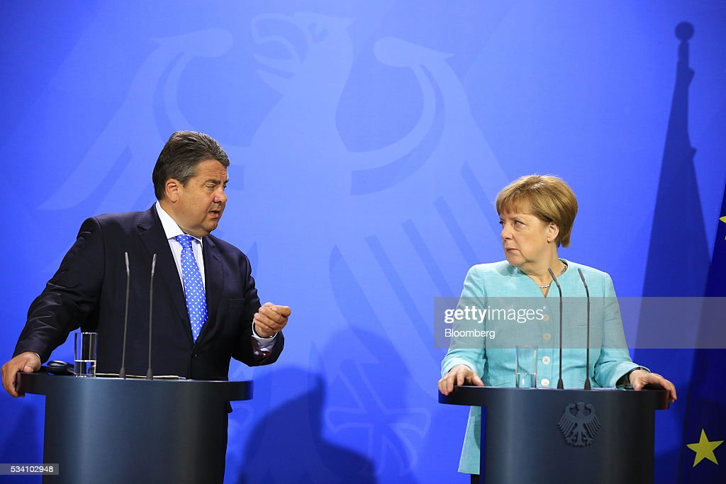 Sigmar Gabriel, Germany's economy and energy minister, left, speaks as Angela Merkel, Germany's chancellor, looks on during a news conference following a two-day cabinet retreat in Meseburg, Germany, on Wednesday, May 25, 2016. In the latest response to the refugee crisis that's dogged Merkel since last summer, her cabinet on Wednesday backed legislation that includes stricter requirements for asylum seekers to integrate into German society. Photographer: Krisztian Bocsi/Bloomberg via Getty Images *** Angela Merkel; Sigmar Gabriel