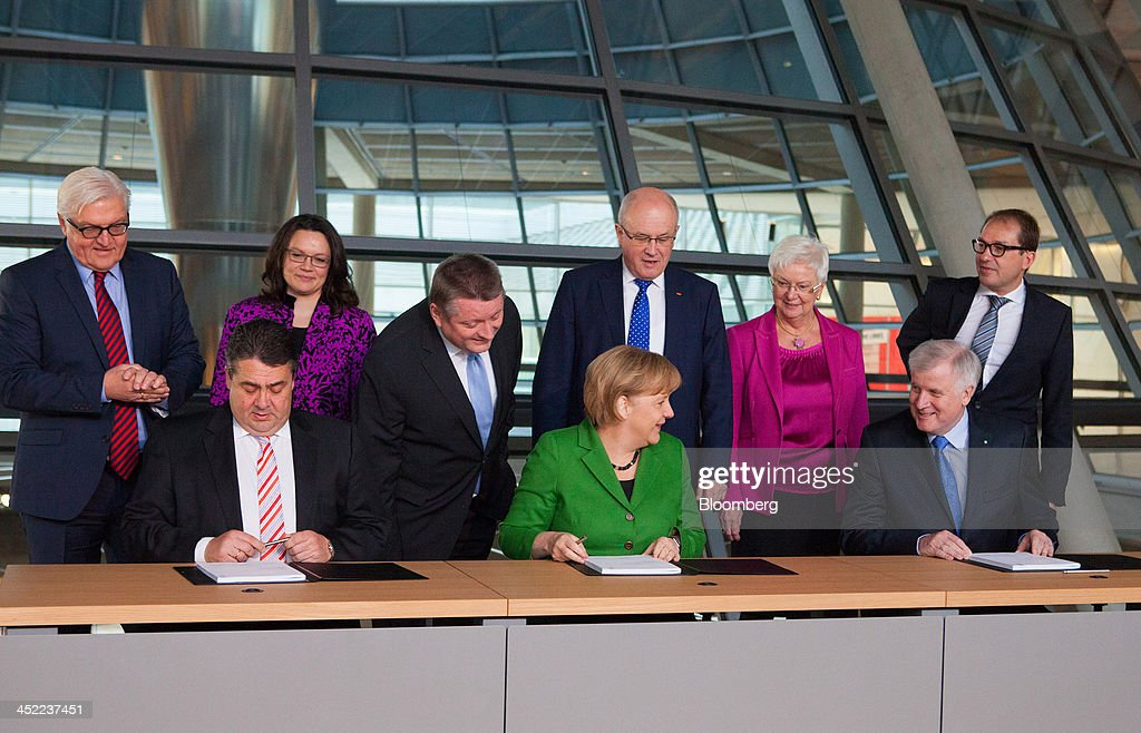 <a gi-track='captionPersonalityLinkClicked' href=/galleries/search?phrase=Sigmar+Gabriel&family=editorial&specificpeople=543927 ng-click='$event.stopPropagation()'>Sigmar Gabriel</a>, head of the Social Democratic Party (SPD), front left, sits with <a gi-track='captionPersonalityLinkClicked' href=/galleries/search?phrase=Angela+Merkel&family=editorial&specificpeople=202161 ng-click='$event.stopPropagation()'>Angela Merkel</a>, Germany's chancellor, front center, and <a gi-track='captionPersonalityLinkClicked' href=/galleries/search?phrase=Horst+Seehofer&family=editorial&specificpeople=4273631 ng-click='$event.stopPropagation()'>Horst Seehofer</a>, who heads Merkel's Christian Social Union (CSU) Bavarian sister party, prior to signing the coalition agreement at the German parliament building, or Reichstag, in Berlin, Germany, on Wednesday, Nov. 27, 2013. Merkel reached an agreement with the Social Democrats on a coalition that would implement a national minimum wage and increase spending on pensions and infrastructure without raising taxes. Photographer: Krisztian Bocsi/Bloomberg via Getty Images