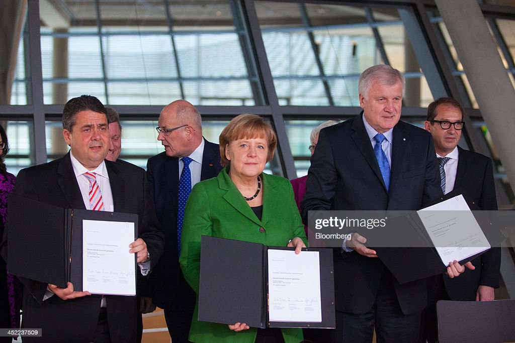 <a gi-track='captionPersonalityLinkClicked' href=/galleries/search?phrase=Sigmar+Gabriel&family=editorial&specificpeople=543927 ng-click='$event.stopPropagation()'>Sigmar Gabriel</a>, head of the Social Democratic Party (SPD), left, stands with <a gi-track='captionPersonalityLinkClicked' href=/galleries/search?phrase=Angela+Merkel&family=editorial&specificpeople=202161 ng-click='$event.stopPropagation()'>Angela Merkel</a>, Germany's chancellor, center, and <a gi-track='captionPersonalityLinkClicked' href=/galleries/search?phrase=Horst+Seehofer&family=editorial&specificpeople=4273631 ng-click='$event.stopPropagation()'>Horst Seehofer</a>, who heads Merkel's Christian Social Union (CSU) Bavarian sister party, as they pose for a photograph holding the signed coalition agreements at the German parliament building, or Reichstag, in Berlin, Germany, on Wednesday, Nov. 27, 2013. Merkel reached an agreement with the Social Democrats on a coalition that would implement a national minimum wage and increase spending on pensions and infrastructure without raising taxes. Photographer: Krisztian Bocsi/Bloomberg via Getty Images