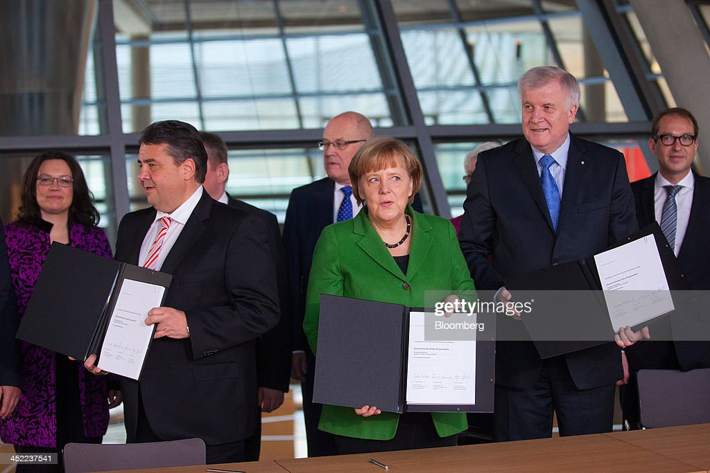 <a gi-track='captionPersonalityLinkClicked' href=/galleries/search?phrase=Sigmar+Gabriel&family=editorial&specificpeople=543927 ng-click='$event.stopPropagation()'>Sigmar Gabriel</a>, head of the Social Democratic Party (SPD), left, stands with <a gi-track='captionPersonalityLinkClicked' href=/galleries/search?phrase=Angela+Merkel&family=editorial&specificpeople=202161 ng-click='$event.stopPropagation()'>Angela Merkel</a>, Germany's chancellor, center, and <a gi-track='captionPersonalityLinkClicked' href=/galleries/search?phrase=Horst+Seehofer&family=editorial&specificpeople=4273631 ng-click='$event.stopPropagation()'>Horst Seehofer</a>, who heads Merkel's Christian Social Union (CSU) Bavarian sister party, as they pose for a photograph holding their signed coalition agreements at the German parliament building, or Reichstag, in Berlin, Germany, on Wednesday, Nov. 27, 2013. German Chancellor <a gi-track='captionPersonalityLinkClicked' href=/galleries/search?phrase=Angela+Merkel&family=editorial&specificpeople=202161 ng-click='$event.stopPropagation()'>Angela Merkel</a> reached an agreement with the Social Democrats on a coalition that would implement a national minimum wage and increase spending on pensions and infrastructure without raising taxes. Photographer: Krisztian Bocsi/Bloomberg via Getty Images