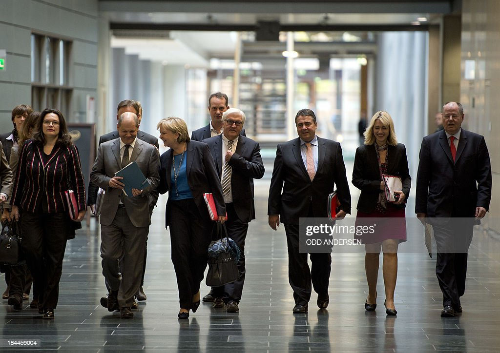 Sigmar Gabriel (3rd R), leader of Germany's social democratic SPD party, and party colleagues Andrea Nahles (L), Olaf Scholz (2nd L), Hannelore Kraft (3rd L), Frank-Walter Steinmeier (4th R), Manuela Schwesig (2nd R) and Peer Steinbrueck (R) walk through a corridor at Jakob-Kaiser-Haus at the German parliament for preliminary talks between German Chancellor Angela Merkel's conservative CDU/CSU union and the social democratic SPD in Berlin on October 14, 2013. The exploratory talks with the left-leaning ecologist party are part of Merkel's hunt for a governing partner after her conservatives won September 22 elections but fell short of a ruling majority.