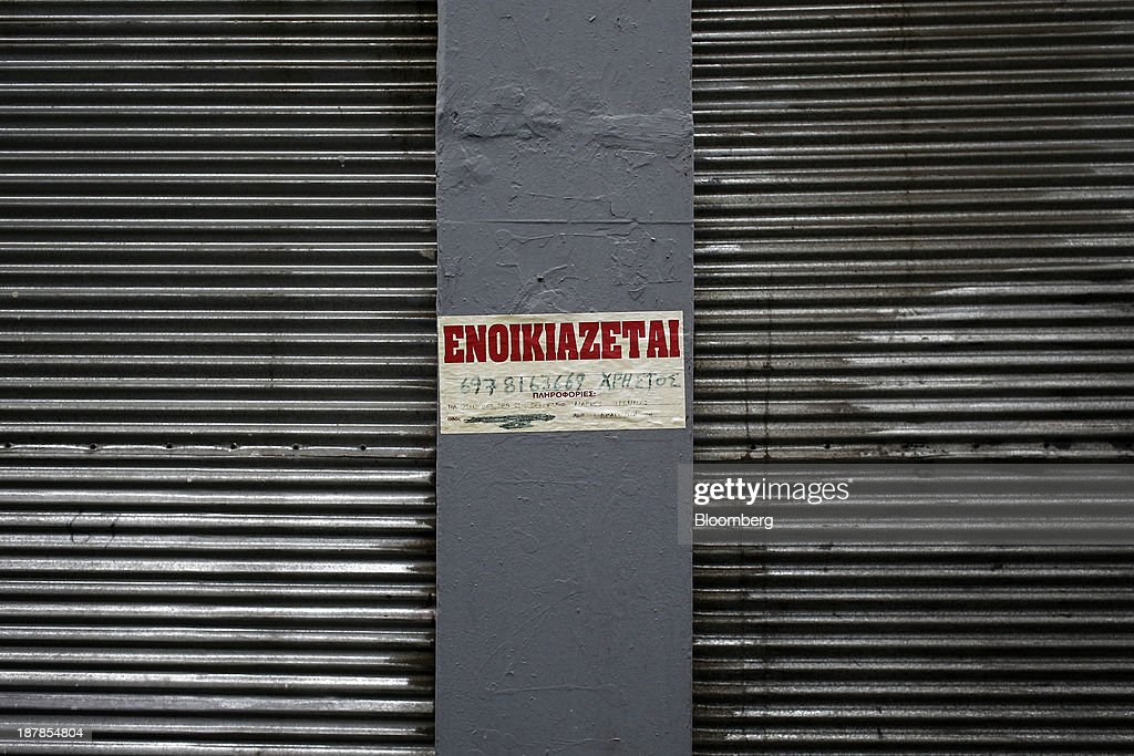 A sign advertises a property 'To Rent' outside a closed store in Thessaloniki, Greece, on Wednesday, Nov. 13, 2013. Greece 'is following a fiscal adjustment program that aims to make the country's public finances sustainable on a permanent basis,' Finance Minister Yannis Stournaras told lawmakers during the debate, after holding talks with the troika earlier in the week. Photographer: Konstantinos Tsakalidis/Bloomberg via Getty Images